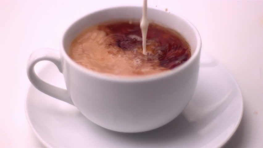 Milk pouring into tea in slow motion