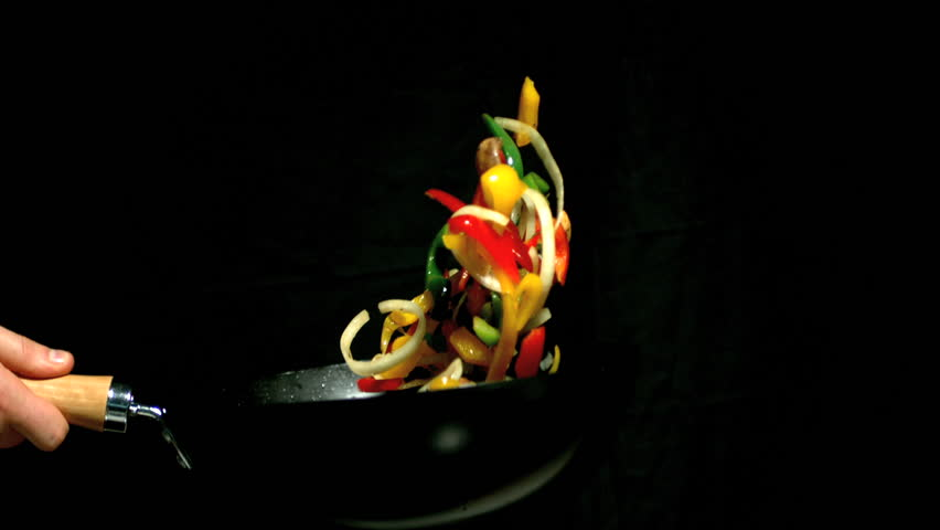 Chef tossing vegetables in wok side view on black background in slow motion