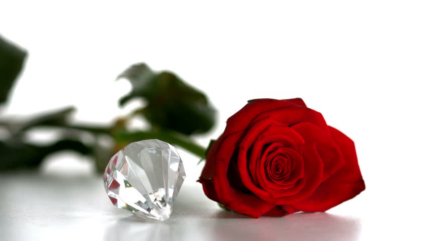 Diamond spinning beside red rose on white background in slow motion