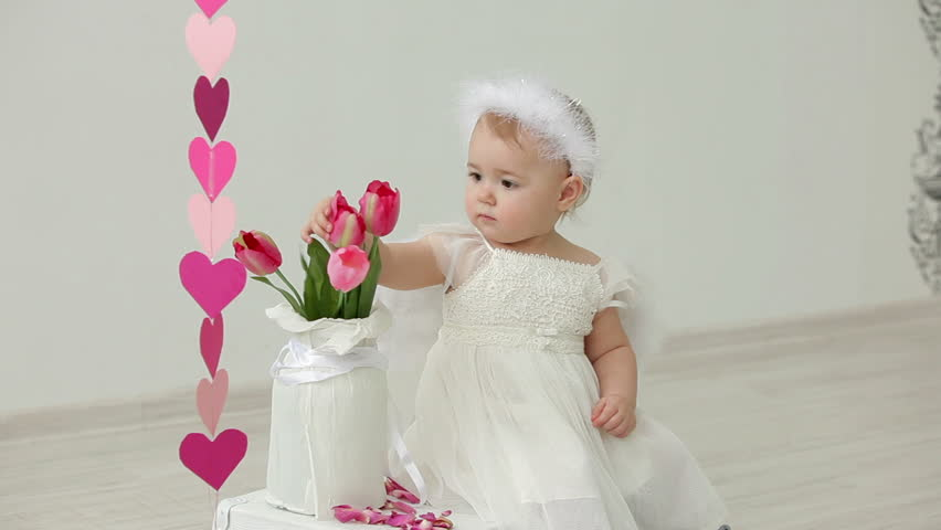 Cute Baby Girl Dressed As An Angel Play With Flowers Stock