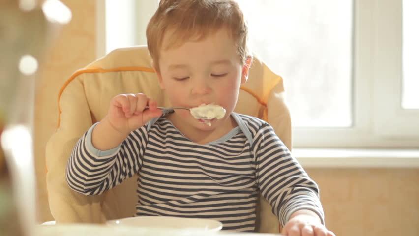 Little boy eats porridge in the morning.