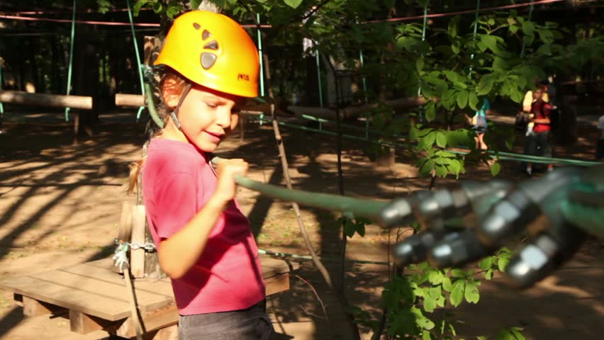 Little girl in helmet climbers by rope at park with people in climbing center, closeup - HD stock footage clip