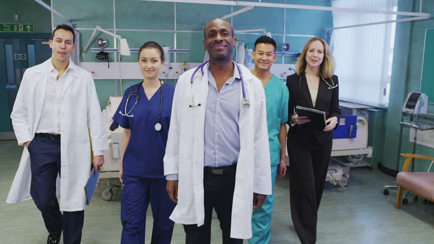 Attractive group of medical personnel of mixed ages and ethnicity stand and pose for a group portrait.