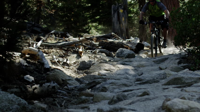 An extreme mountain biker speeds through the forest on a bike trail in the wilderness during the day in slow motion