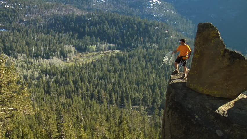 A male climber throws a safety rope over the ledge