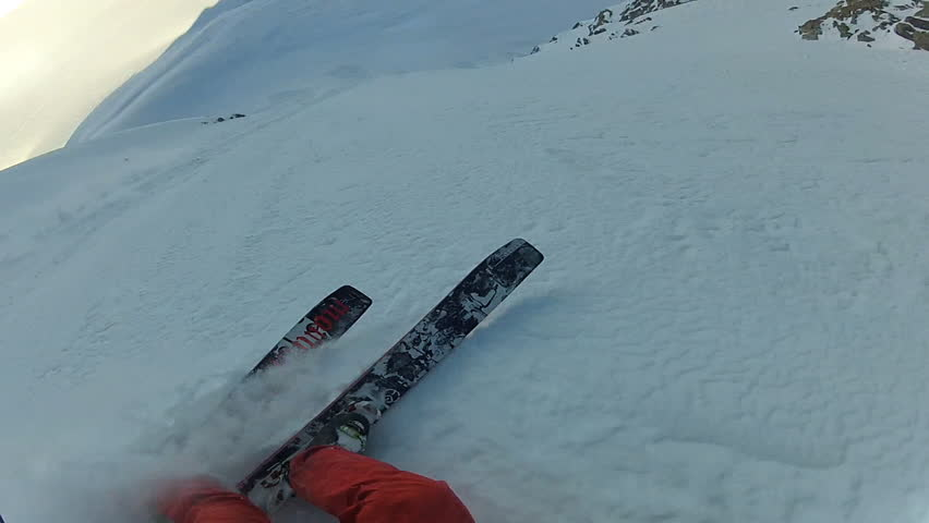 A skier carves back and forth as he rides down a mountain covered in fresh powder during the day. It is shot with a camera mounted to the athletes head and provides a POV, point of view, perspective.
