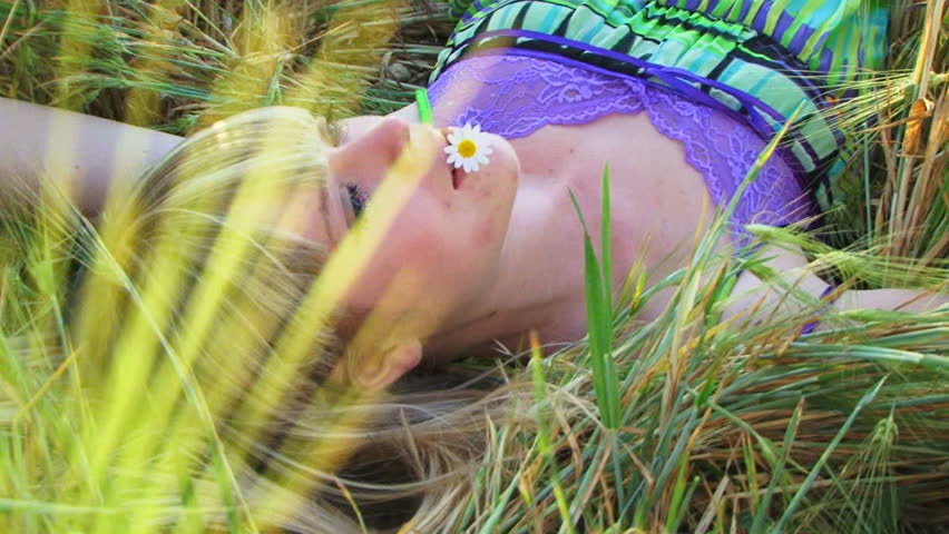 Young Woman Laying In A Field Of Wheat. Among Ears Of ...