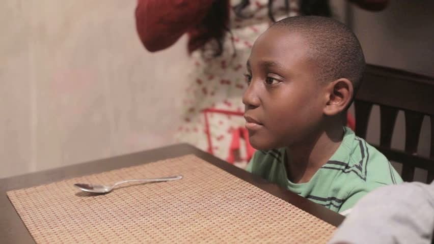 African American Black mother serving tomato soup to her son at the dinner table in the kitchen - HD stock footage clip