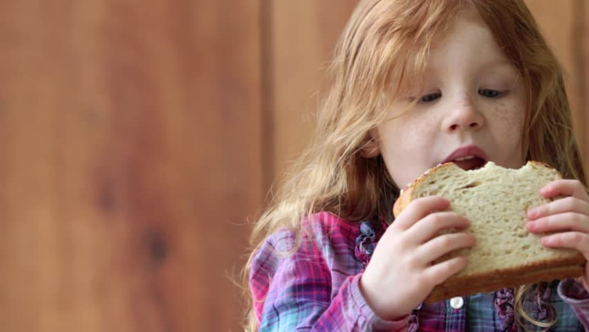 Redheaded girl eating peanut butter and jelly sandwich