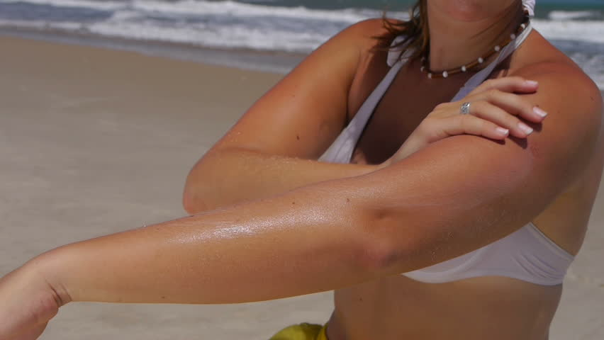 Woman applying sun block on the beach