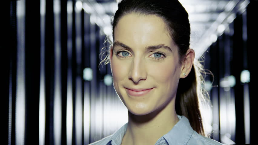 Portrait of a female IT engineer who is working in a data center with rows of server racks and computers.
