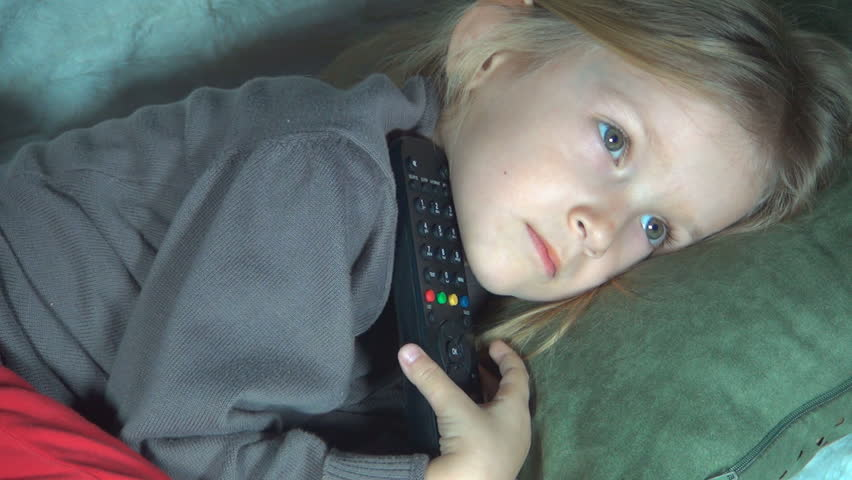 Zoom Out of Child Watching TV, Little Girl Lying on Couch with Remote, Children - HD stock footage clip