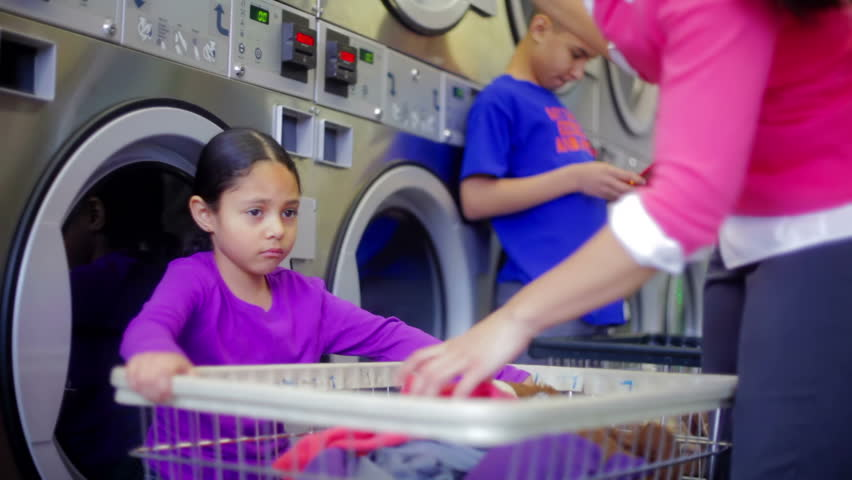 Latina Mom and child doing laundry together putting clothes in the dryer in the laundromat