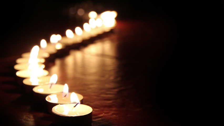 Candlelight. Little candles lined up light up one by one. - HD stock footage clip
