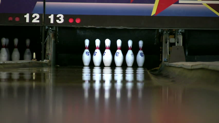 Ball rolls down a bowling lane for a strike.