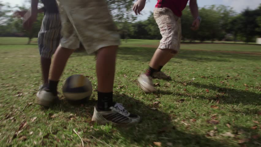 Children playing football match, group of young kids having fun with soccer game in park. Sequence, low angle view - HD stock video clip