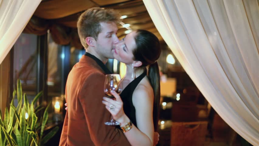 Young couple slowly dance with glass of wine near curtain in restaurant - HD stock video clip