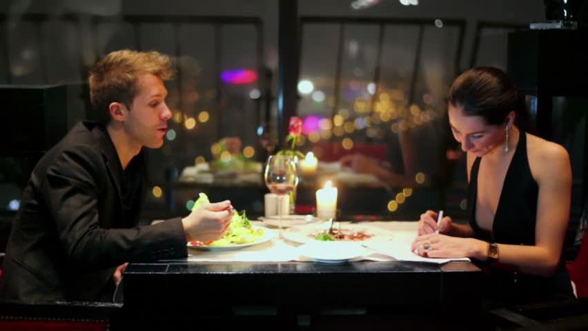 Blond man eats at table and young woman read document near window in restaurant - HD stock video clip