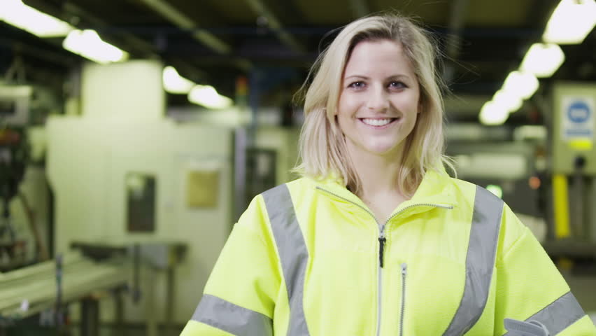 Portrait of a cheerful and friendly female warehouse manager who is wearing a hard hat and reflective clothing. She takes off her hard hat and smiles at the camera.  In slow motion.