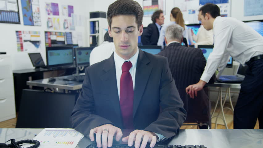 A young businessman is engaged in a video call with a client as seen from the pov of the computer screen. He is sitting at his desk in a busy office filled with computers. In slow motion.
