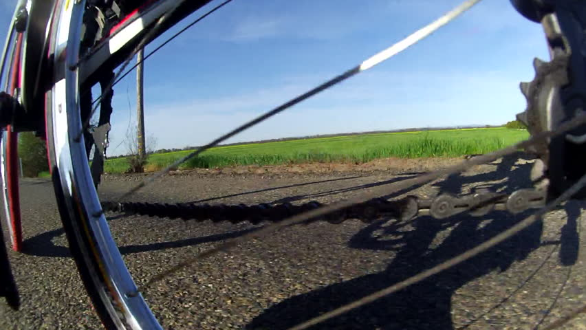 UNIQUE LOW ANGLE POV OF CYCLIST PEDALS, WHEELS, SPROCKETS WHILE RIDING BICYCLE ON COUNTRY ROAD 1920 X 1080 HD HIGH DEFINITION  STOCK VIDEO FOOTAGE CLIP - HD stock video clip