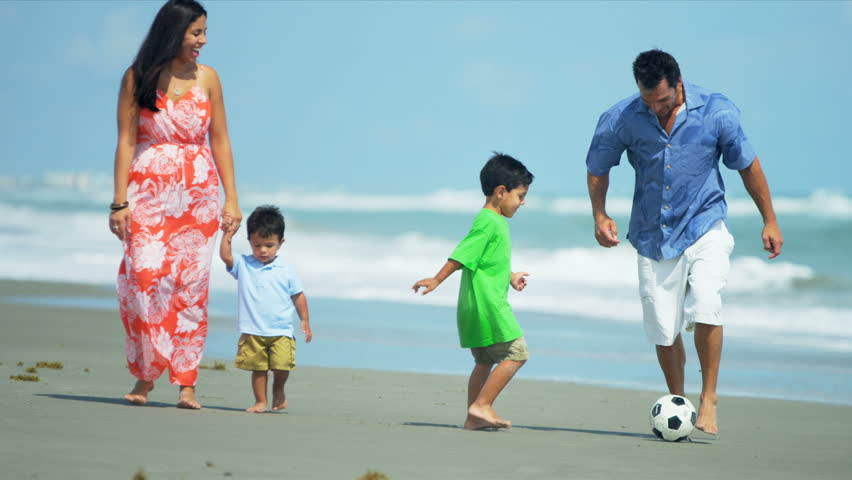 Diverse attractive loving family spending holiday on beach playing soccer shot on RED EPIC