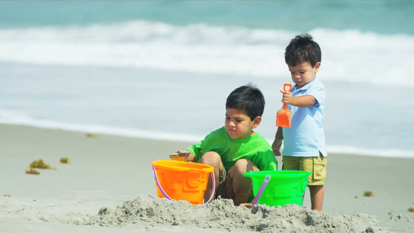 Little Hispanic brothers playing together with young father on beach shot on RED EPIC - HD stock video clip