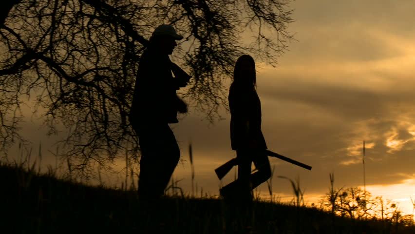 A pair of hunters, in silhouette, walk with their guns, at sunset. - HD stock footage clip