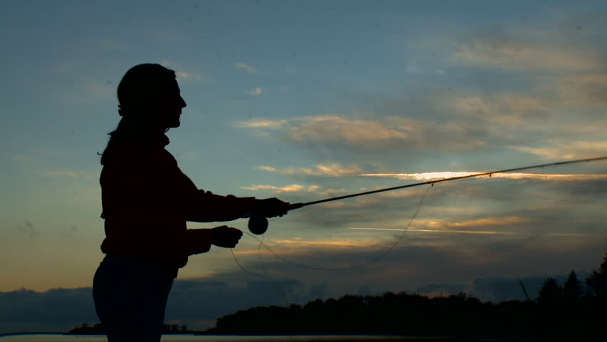 Silhouette of a woman fly-fishing at sunset.