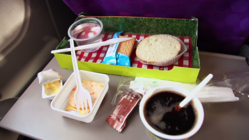 Hand mixes coffee in cap on table with other food at plane - HD stock video clip