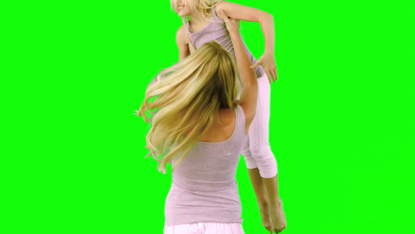 Mother lifting and spinning her daughter on green screen in slow motion - HD stock video clip