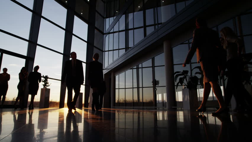 Silhouettes of a diverse group of business people walking through a modern glass fronted building at sunset.