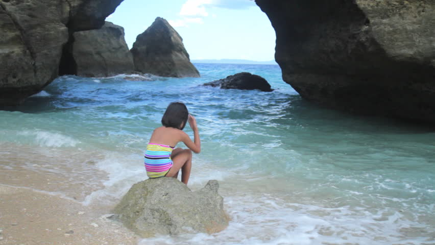 Young girl in the beach playing with sea water. - HD stock video clip