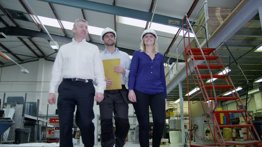 Happy and friendly team of workers in a warehouse or factory come together as they walk around the factory floor. They may be the owners of the business or part of the company team.