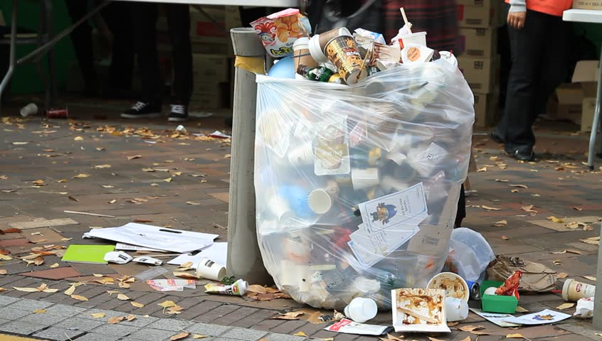 Trash spilling out of overfilled trash plastic bag on city street