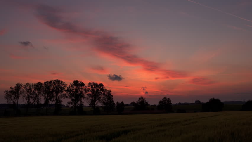 Wide angle time lapse shot of a rural sunrise with dark red glowing colours.