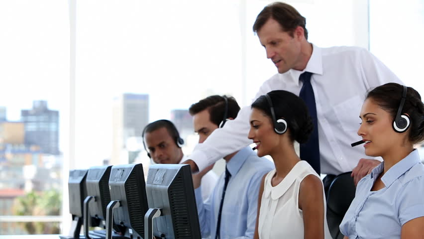 Businessman explaining the work to his employees in a call centre