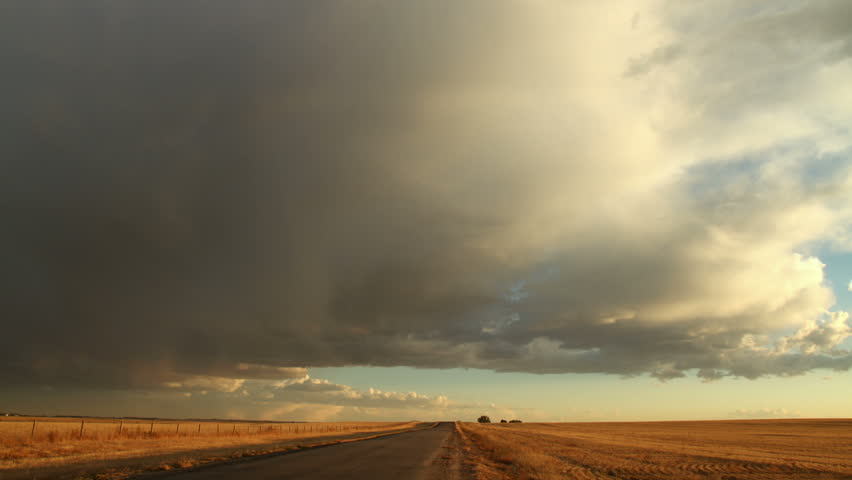 Storm Clouds over Rural Dirt Road and Meadow. HD 1080p timelapse