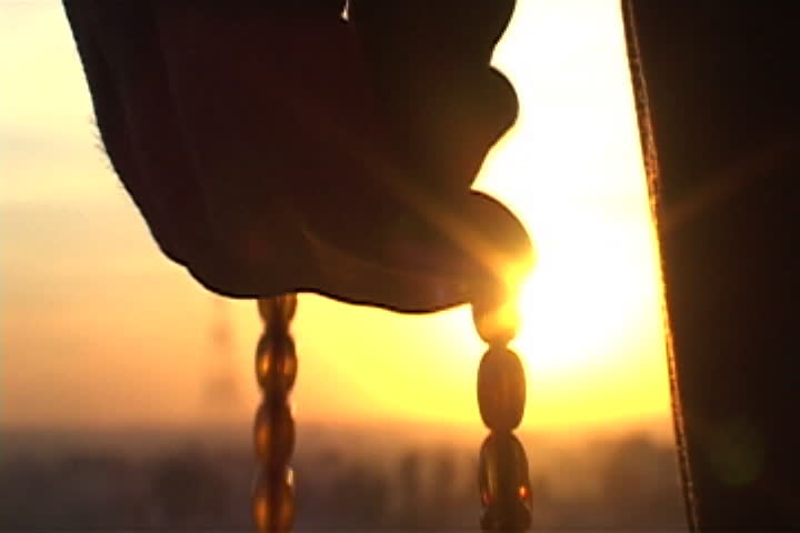 Silhouette of hand counting off prayer beads with bright orange setting sun in background in Mosul, Iraq.