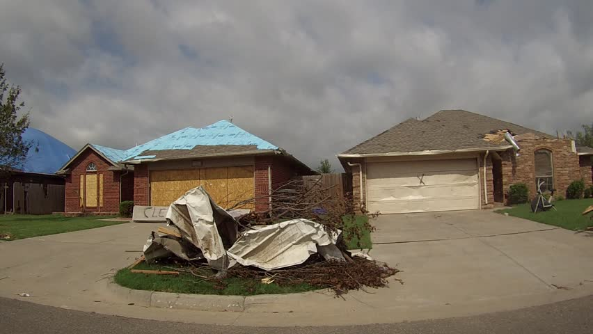 MOORE, OK - MAY 20, 2013: This was a neighborhood in Moore, Oklahoma after the EF5 tornado hit on May 20, 2013.  Houses are turned to ruble.  Destroyed cars litter the street and yards.  Trees are stripped of leaves and bark.