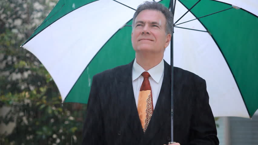 A businessman is unconcerned with the rain because he has the protection of his large umbrella. - HD stock footage clip