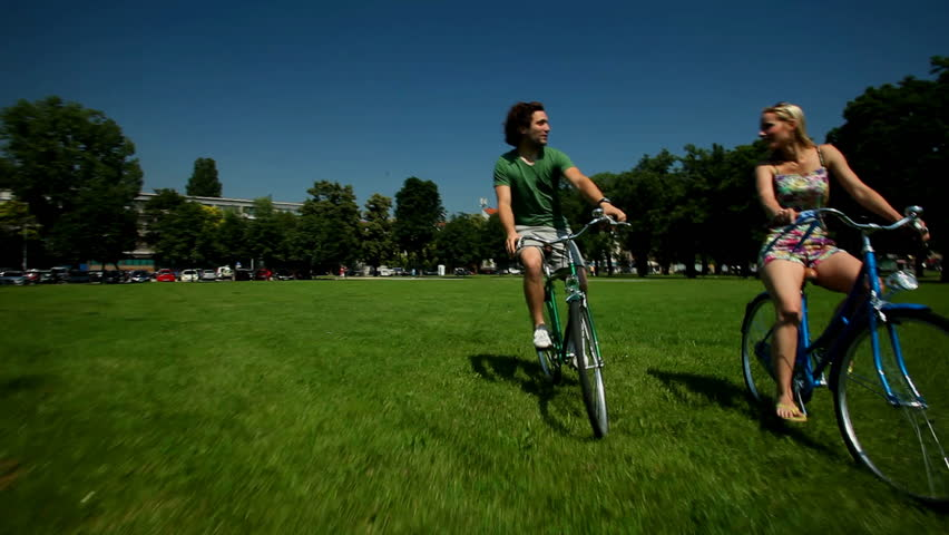 Young couple enjoying cycling through park in summer