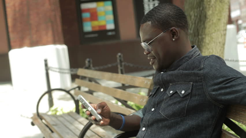 Black guy reading an email and text message on his cell phone