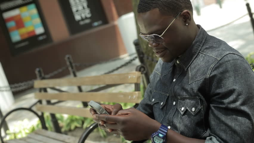 Black guy texting on his smart phone