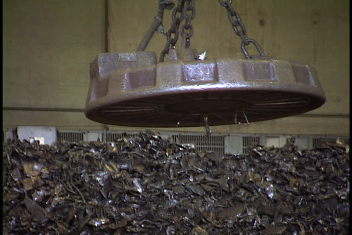 Large magnet is lowered, picks up steel pieces from pile, is raised and carried across foundry interior in St. Cloud, Minnesota.