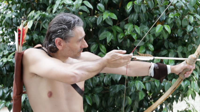 shirtless man with primitive bow - HD stock footage clip