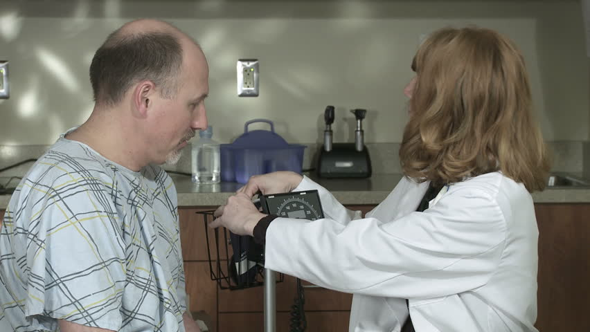 Mid shot of female doctor taking the blood pressure of a mature male patient. - HD stock footage clip