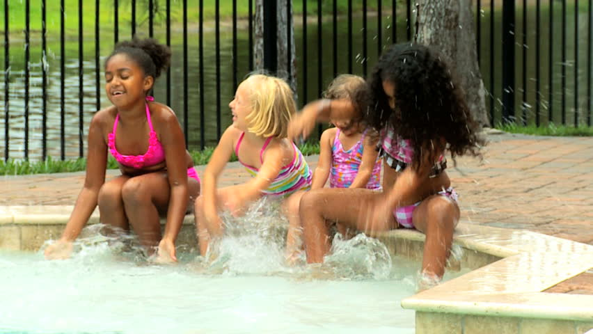 Little Caucasian African American childhood friends enjoying healthy outdoor activity in water swimming pool