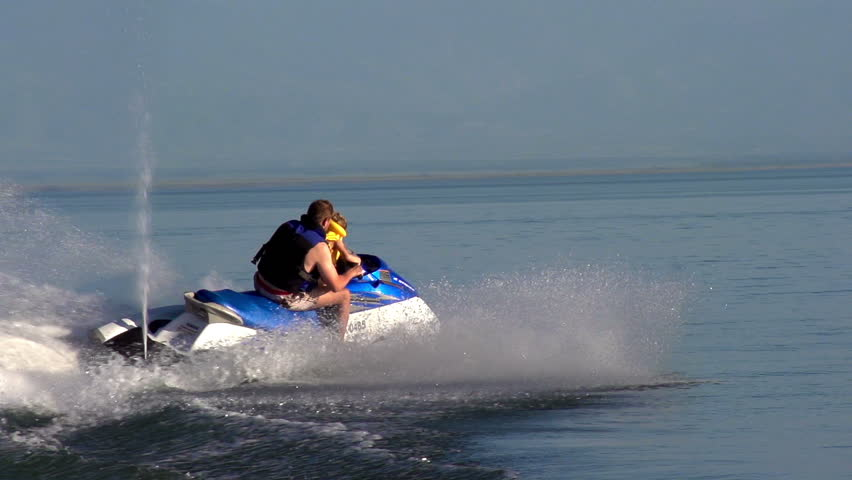 Water Activities. The man rolls the small son on a jet ski.  Motion at a rate of 240 fps