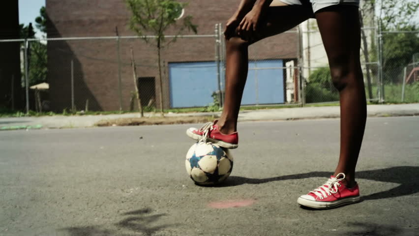 person playing outdoor kicking a soccer ball with sneakers on outside in the street